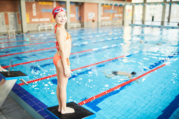 Happy little girl in swimsuit, swim-cap and goggles looking at camera while learning to dive into water of swimming-pool