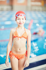 Little girl in bikini, swim-cap and goggles looking at camera with swimming-pool on background