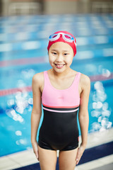 Cheerful child in swimwear looking at camera with swimming-pool behind