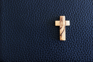Cross on black leather background