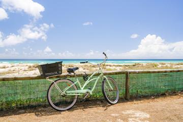 A bicycle leans against a fence at Kirra Beach, Gold Coast, Queensland, Australia.