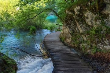 Beautiful view of waterfalls with turquoise water and wooden pathway through over water. Plitvice Lakes National Park, Croatia. Famous attraction, summer landscape.