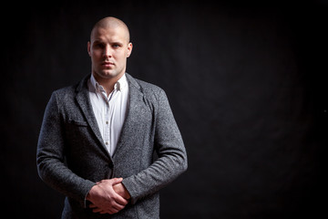 A young bald man in a white shirt, gray suit confidently looks at the camera and holds his hands on his jacket on a black isolated background
