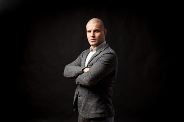 A young bald man in a white shirt, gray suit confidently looks at the camera and holds his arms crossed on his chest on a black isolated background