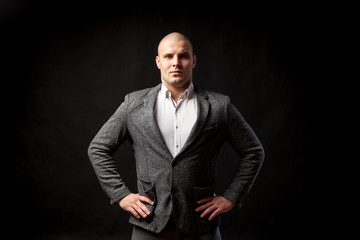 Young bald man in white shirt, gray suit confidently looks at camera and posing on black isolated background