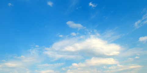 Light cumulus clouds against the blue sky. Wide photo.