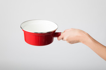 Hand holding a  single-handled pot.
