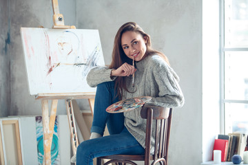 Young woman artist painting at home creative biting paint brush