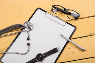 Workplace of doctor - stethoscope and other supplies on the yellow wooden desk