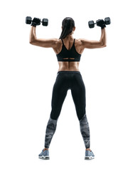 Young woman bodybuilder doing exercise with dumbbells. Photo of sporty woman in training pumping up muscles of the back and hands on white background. Rear view. Full length