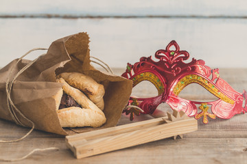 Purim jewish holiday composition with hamantaschen, purim mask and purim gragger on a vintage wood background with copy space