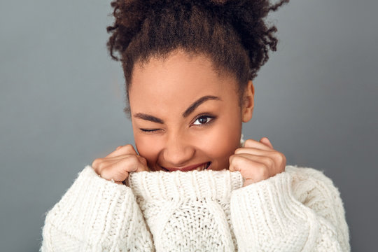 Young african woman isolated on grey wall studio winter concept wink
