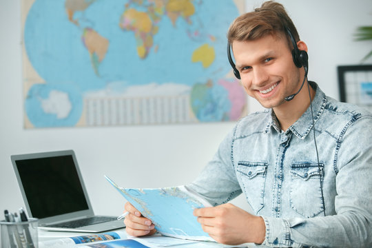 Young male travel agent consultant in tour agency holding map