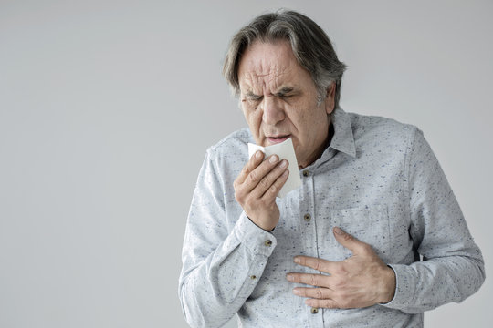 Old man coughing to tissue
