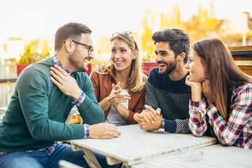 Group of four friends having fun a coffee together. Two women and two men at cafe talking laughing and enjoying their time Wall mural