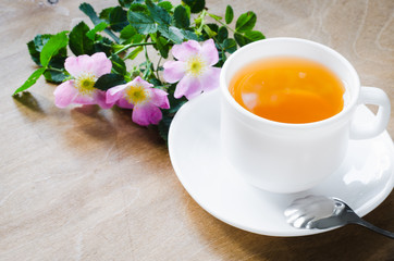 Cup of morning tea with lemon and delicate flowers