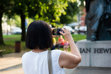 Gdansk, Poland - August 10, 2017: Woman taking photo at her smartphone of statue of polish astronomer Jan Heweliusz. Monument of astronomer Johannes Hevelius with historical architecture of Gdansk.