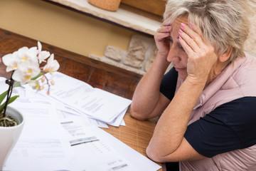 Ältere Frau sitzt vor vielen Rechnungen und ist verzweifelt, Konzept Geldnot und Finanzen