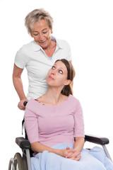 Junge Frau im Rollstuhl mit Pflegerin im Studio, freigestellt vor weiß