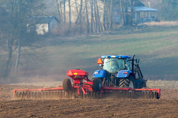 Tractor working with cultipacker rollers on the field