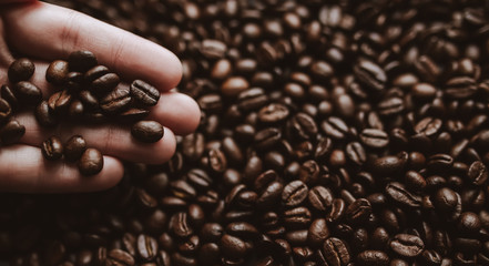 Roasted coffee beans in human hand. Abstract background
