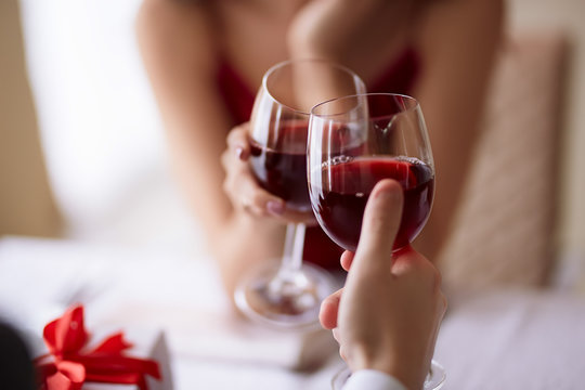 Beautiful couple celebrating Valentine`s day in restaurant, drinking wine, sharing gifts and enjoying each other.
