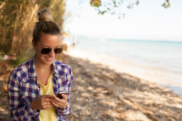 Girl on the beach looking on mobile phone