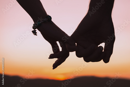 silhouettes of female and male hands holding hands against