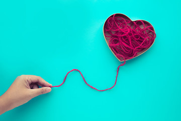 Heart shape from red yarn,rope with female hand on blue background.