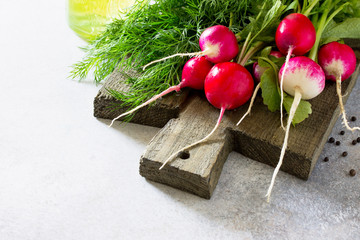 Radish. Red fresh radish, olive oil and fresh herbs on a stone or slate background. The concept of healthy and dietary nutrition. Copy space.