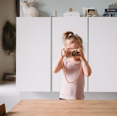 Little girl taking picture with toy camera