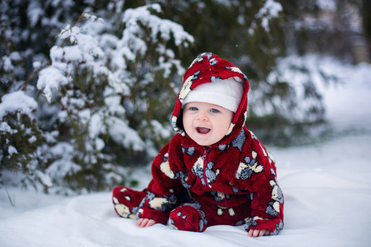 Little cute smiling baby boy, sitting outdoors in the snow