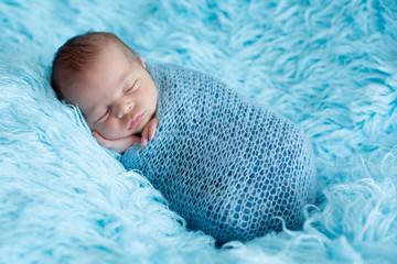 Cute baby boy, peacefully sleeping wrapped in brue wrap on a blue fur