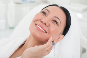 Close up portrait of delighted senior lady touching her face. She is lying on daybed in beauty salon and smiling