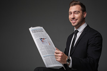 Portrait of cheerful unshaven businessman reading newspaper. He looking at camera. Rest and information concept. Isolated