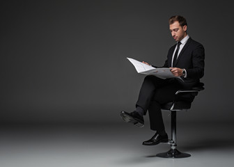 Full length portrait of calm unshaven businessman reading newspaper while sitting on chair. Rest and job concept. Copy space