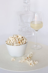 Salt popcorn and glass of wine on white background for relaxed evening with movie