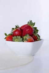 Fresh strawberries in a ceramic bowl on white background.
