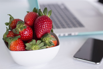 Laptop and strawberries on white background