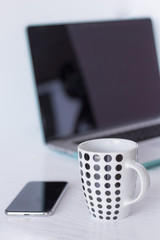 Laptop and coffee in home office on white background