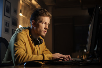 Side view serene unshaven programmer typing in keyboard of digital device while sitting at table. Profession concept
