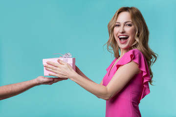Portrait of excited young woman getting gift from man. She is standing and smiling. Isolated