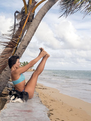 girl is engaged in gymnastics on the beach, dogs are near