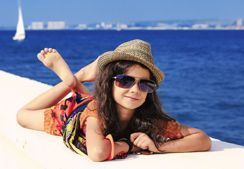 A girl in bright clothes and a straw hat lies and rests on the beach on the pier