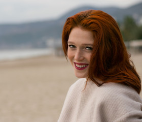 A nice  girl with a beautiful smile is sitting on the beach. A woman with red hair and freckles. Vacation lifestyle