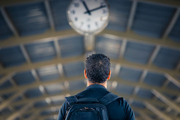 Man with backpack waiting under a clock in a train station