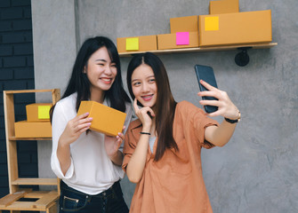 Teamwork asian women freelancer and blogger review product working sme business at home office with parcel box for delivery online to customer by talking smartphone live recording video on social