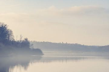 Lake scenery with morning fog and silent water