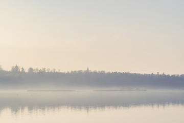 Mist hanging over a quiet lake in the early morning