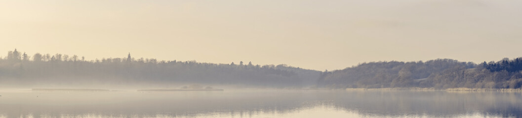 Panorama view over a misty lake in the morning sun